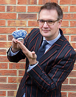 BNPS.co.uk (01202 558833)<br /> Pic: Hansons/BNPS<br /> <br /> Auctioneer Charles Hanson with the bowl<br /> <br /> A tiny finger bowl which was spotted in a box of bric-a-brac has sold for over £32,000 after it was found to be a rare Chinese relic.<br /> <br /> The blue and white bowl, that measures 5ins in diameter, was made during the reign of China's Emperor Yongzheng, which lasted from 1722-35 during the Qing Dynasty.<br /> <br /> The item was brought into an auction house by a woman who had inherited it from a relative.<br /> <br /> Auctioneer Charles Hanson identified the six-character mark on the bottom that confirmed it was made in imperial China in the early 18th century.