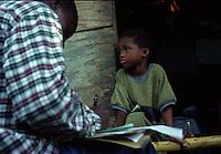 COLOMBIA  - Buenaventura -villaggio nella foresta colombiana  utilizzato per lo studio della malaria dall'OMS in quanto presenti le principali specie di zanzare anofele. Nell'immagine: un medico prepara i documenti prima della vaccinazione, un ragazzino in attesa sulla soglia della capanna.