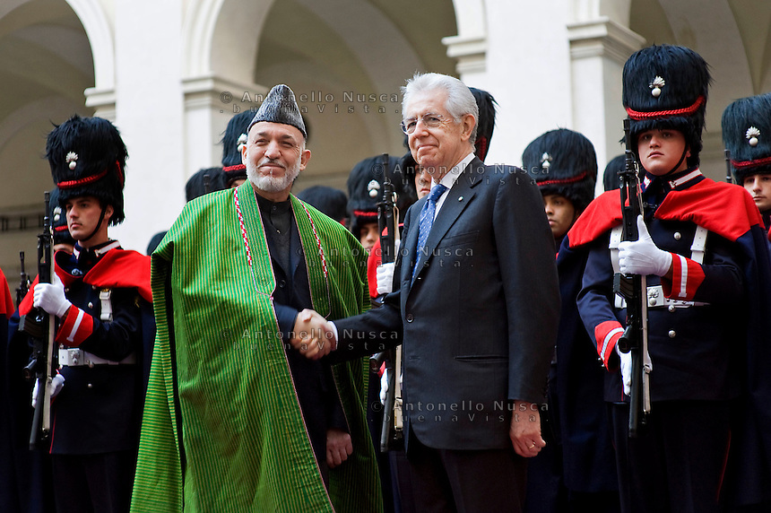 Il Presidente dell'Afghanistan Hamid Karzai con Mario Monti a Palazzo Chigi..Afghan President Hamid Karzai (L) and Italian Prime Minister Mario Monti shake hands during a meeting to sign a bilateral agreement on cooperation and partnership, at Palazzo Chigi in Rome. Italy is the first western country to have signed a cooperation agreement with Afghanistan.