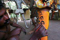 A painter paints a leg of a Pulikali performer, Trichur, Kerala, India..Pulikali or Kaduvvakali is a two hundred year old folk dance form, practised mostly in Thrissur and Palghat districts of Kerala. It liberally makes use of forms and symbols of nature that finds expression in its bright, bold body painting and high-energy dance movements. The philosophy of Pulikali is that human and nature are integral parts of each other. So by fusing man and beast in its artistic language, it flamboyantly celebrates the connection. Arindam Mukherjee