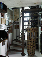 An iron spiral staircase winds its way up from the basement level, the walls lined with artworks
