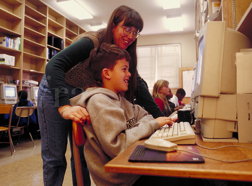 Elementary shool student and teacher in a computer lab.