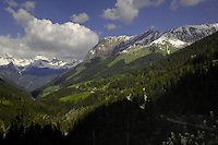 Clouds above snow covered peaks with forest foreground. Hahntennjoch pass between Imst and Reutte  Tyrol/ Tirol, Austria. The Alps.