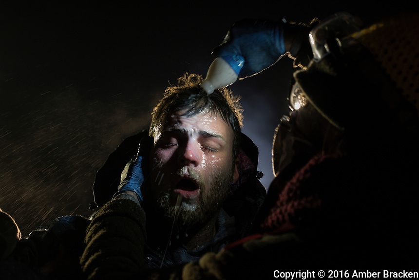 Healers - A man is treated after being pepper sprayed by police. White people have joined the camps in large numbers, often standing in front of indigenous protestors to shield them with their bodies. <br /> <br /> A man is treated with milk of magnesia after being pepper sprayed at the police blockade on highway 1806 near Cannon Ball, North Dakota on Sunday, November 20, 2016. Many people were injured when, with temperatures below freezing, police deployed water canons, pepper spray, tear gas, rubber bullets and percussion grenades. Amber Bracken