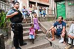 Le policier De Luca converse avec des habitants de la favela Morro da Formiga au pied des escaliers où l'on distingue encore un impact de balle de fusil. Il y a quelques mois, avant l'installation de l'UPP, l'endroit était un des points critiques de la communauté du fait de la guerre que se livraient les narcotrafiquants du Comando Vermelho (CV) avec ceux du Morro do Borel, situé juste en face.
