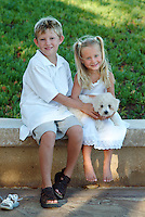 Brother and sister with small bichon frise puppy