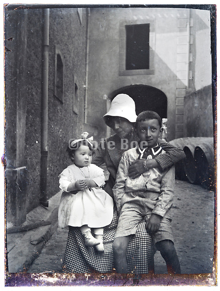 mother posing with children in outdoors setting glass plate 1900s