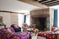 The colourful living room was inspired by a Russian folk house and the seating is covered in bright Afghan throws