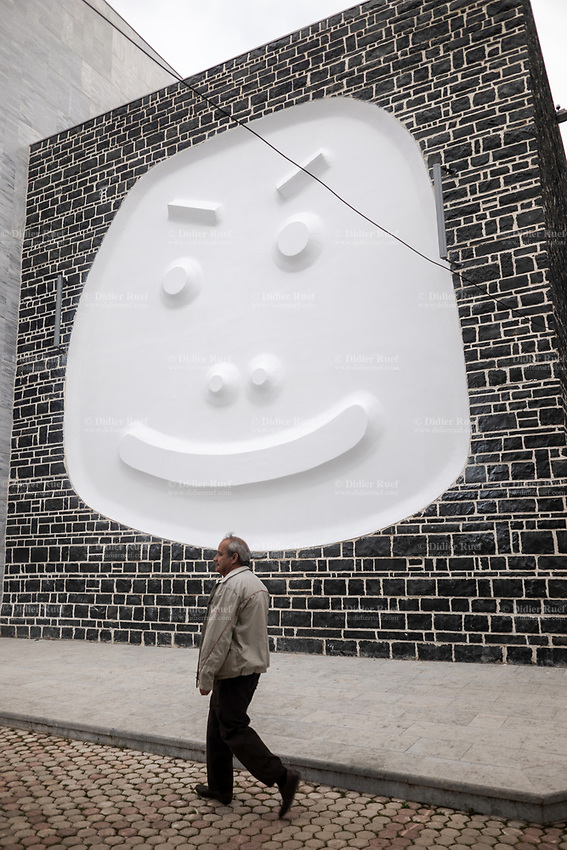 Albania. Korçë. An elderly man with grey walks by a mural to the newly renovated theater. Smiley face. Korçë is a city and municipality in southeastern Albania. 21.05.2018 © 2018 Didier Ruef