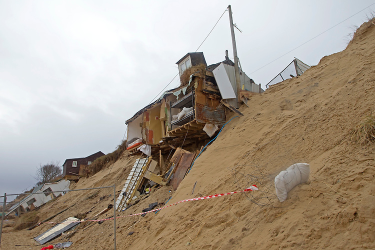 Eroded cliffs and damaged chalets following tidal surges of December 2013, Hemsby, Norfolk UK