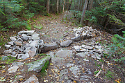 Non-conforming stone structures (wall) along the Mt Tecumseh Trail in the New Hampshire White Mountains during the summer of 2011. Water bar across trail is per guidelines. Trail maintenance handbooks suggest the best trails show little evidence of trail work and that work should blend in with the surroundings. After a trail inspection by Forest Service in June 2012, the walls on each side of the drainage may be removed because they have no real use.
