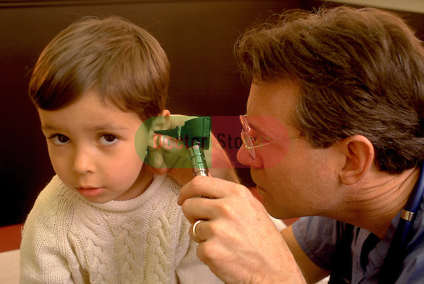 doctor examining ear of young boy with otoscope