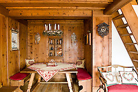 The dining table is neatly placed in a panelled alcove in this traditional chalet which has been restored using salvaged materials