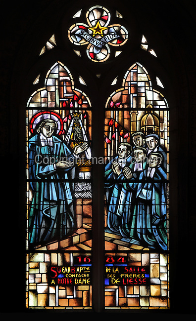 Stained glass window of St Jean-Baptiste de la Salle, 1945, showing the saint on the left and on the right, new clerics joining his order in front of the altar of Notre Dame de Liesse, in a chapel in the Basilica of Liesse Notre Dame, built 1134 in Flamboyant Gothic style by the Chevaliers d'Eppes, then rebuilt in 1384 and enlarged in 1480 and again in the 19th century, Liesse-Notre-Dame, Laon, Picardy, France. Pilgrims flock here to worship the Black Virgin, based on Ismeria, the Soudanese daughter of the sultan of Cairo El-Afdhal, who saved the lives of French knights during the Crusades, converted to christianity and married Robert d'Eppes, son of Guillaume II of France. Picture by Manuel Cohen