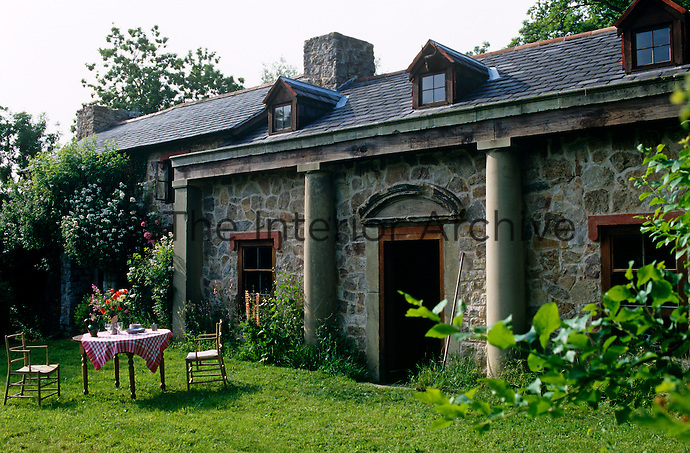 A table in the garden is placed in front of the massive concrete pillars of this country cottage