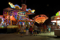 Amusement park at night - mideway attractions and roller ride in motion, Austin, Texas
