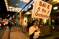 "French horn player Julie Spencer pickets the Fox Theatre with other members of the Atlanta Ballet Orchestra during a performance of ""The Nutcracker."" Last summer the Atlanta Ballet announced it would begin using recorded music for all of its productions and fired the orchestra. The American Federation of Musicians Local 148-462 has filed an unfair labor practice complaint."