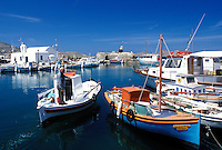 Greece, Paros, Greek Islands, Naoussa, Cyclades, Europe, Fisherman trolling on his fishing boat along the waterfront on Naoussa Harbor on Paros Island on the Aegean Sea.