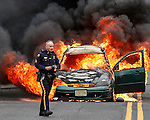 MANASQUAN, NJ — April 1, 2016 — Manasquan Police Sgt. Michael Stoia on scene as a 2000 Ford Focus becomes fully engulfed in flames about 9:40am on Broad Street, here. The driver of the vehicle, Nancy Trapani of Belmar, was not injured.  photo by Andrew Mills
