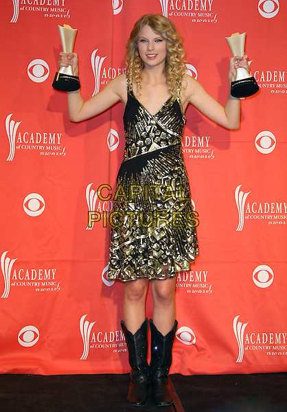 TAYLOR SWIFT.Pressroom at the 44th Annual Academy Of Country Music Awards held at the MGM Grand Garden Arena, Las Vegas, Nevada, USA..April 5th, 2009.full length black gold beads beaded dress awards trophy trophies arms in air boots cowboy .CAP/ADM/MJT.© MJT/AdMedia/Capital Pictures.