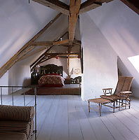 A spacious attic bedroom with exposed roof beams and trusses and a painted wooden floor. A double bed stands at one end and a wrought iron bedstead with striped cushions and a steamer chair provides seating.