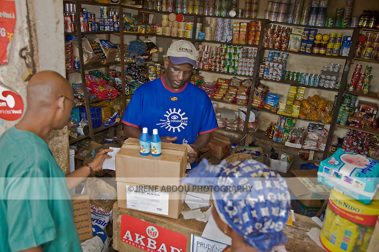 "A wholesaler in Conakry, Guinea logs in bottles/boxes of ""Sur'Eau,"" a chlorine product that makes water safe to drink.  Sur'Eau is distributed by the international social marketing organization, Population Services International."