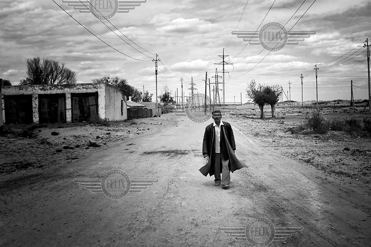A man walks along an empty road. During the 1950s and the 1960s the rivers that feed the Aral Sea (the Amu Darya and the Syr Darya) were diverted for irrigating cotton and other crops. This caused the lake to shrink uncovering sediments heavily polluted with industrial fertilizers that were washed into the lake over the preceding decades. Without the lake's water to contain it these toxic particles were spread by the wind and have caused numerous health problems in surrounding communities. Furthermore, as the lake evaporated the remaining water became increasingly saline and unable to sustain life, destroying the fishing industry. Muynak, once a thriving fishing port, became a depressed and dusty town far from the receding shore.