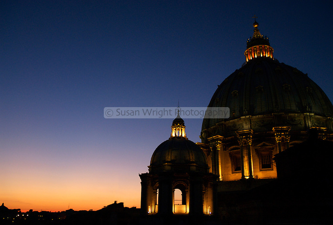 The dome of Saint Peters Basilica in the Vatican in Rome is illuminated against the glow of the setting sun
