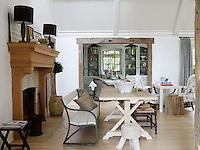 Uneven reclaimed beams frame the doorway leading from the open plan living room into the dining room