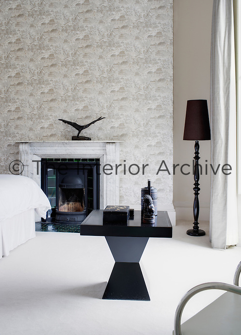 A guest bedroom decorated in elegant shades of grey and white. A contemporary table contrasts with an original period fireplace.