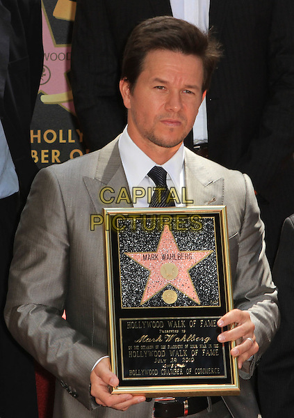 MARK WAHLBERG .Mark Wahlberg is honored on The Hollywood Walk of Fame with the 2414th Star, Hollywood, CA, USA, .29th July 2010..half length grey gray suit tie shirt holding frame white black stubble facial hair .CAP/ADM/FS.©Faye Sadou/AdMedia/Capital Pictures.