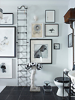The decorative theme of the black and white bathroom is reinforced with photographs by George Dureau and drawings by a variety of young artists
