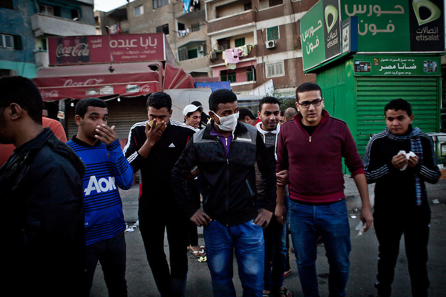 EGYPT, Cairo : People around the al-Azhar university try to breathe after being under tear gaz during clashes with students who support the Muslim Brotherhood and riot police in Cairo's eastern Nasr City district on December 27, 2013. VIRGINIE NGUYEN HOANG