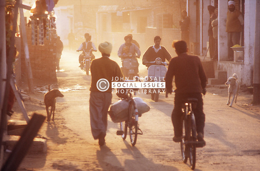 Evening street scene in Gobindigarh; Punjab India with bicycles; scooters and dogs,