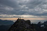 Female climber on summit of Stjerntind, highest peak of Flakstad community, Flakstadøy, Lofoten Islands, Norway
