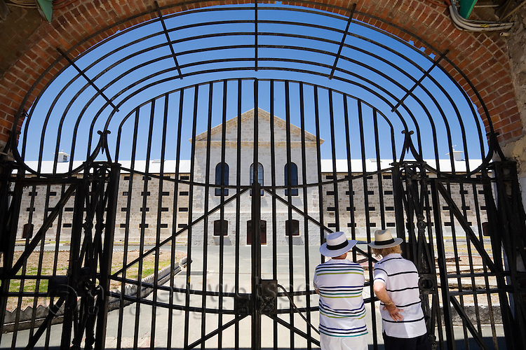 Visitors looks through the gates of the Old Fremantle Prison.  Built by convict labour in 1855, the prison operated until 1991 and now offers prison tours.  Fremantle, Western Australia, AUSTRALIA.