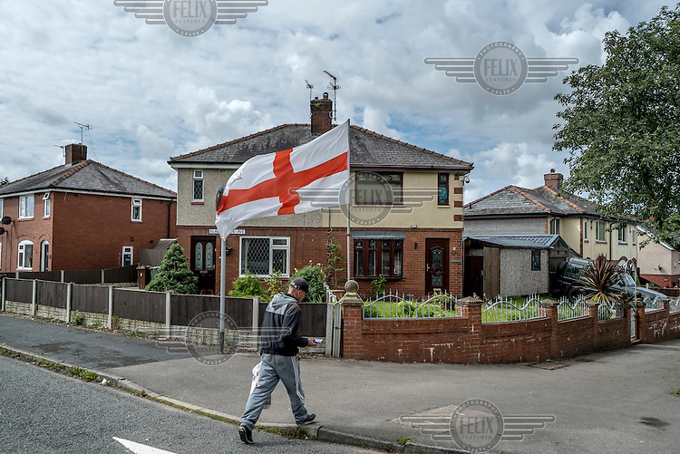 The English flag (Cross of St George) flies outside a house in a suburb of Wigan.