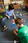 Elementary School New York Grade 4 two boys using paper cut into pieces to represent fractions mathematics lesson vertical