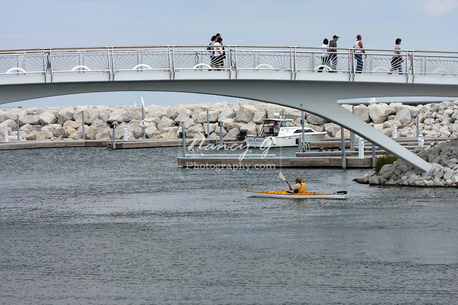 At the Milwaukee Lakefront on Lake Michigan visitors are enjoying the decorative bridge and kayaking the lake