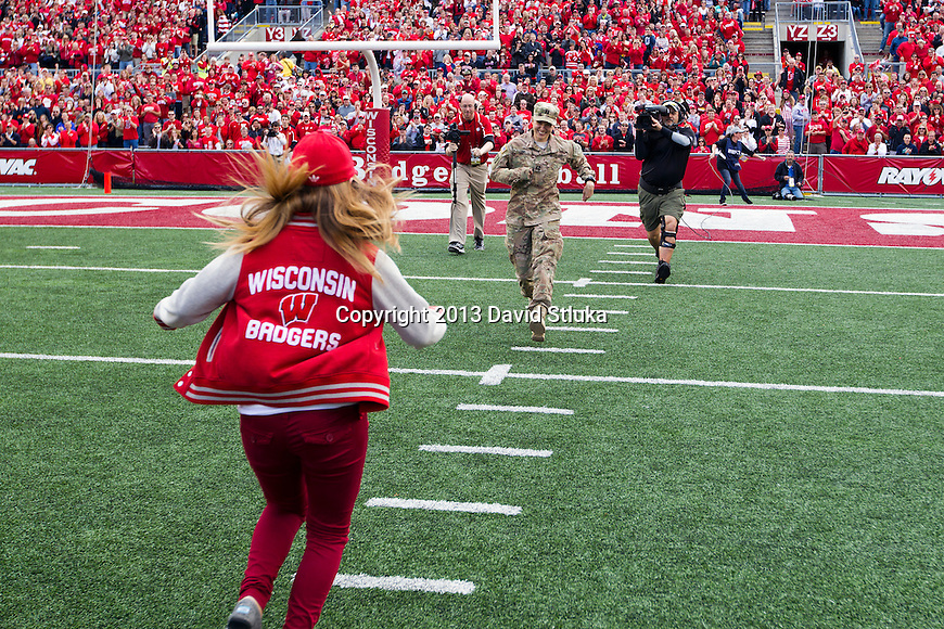 U.S. Army Reserves Captain Jane Renee Lund surprises her daughter from a tour of duty in Afghanistan, during an NCAA Big Ten Conference football game against the Purdue Boilermakers on Saturday, September 21, 2013, in Madison, Wis. The Badgers won 41-10. (Photo by David Stluka)