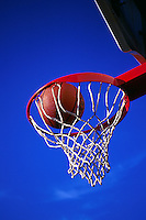 Graphic image of a basketball as it decends into the net; high color contrast of hoop and sky.