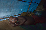 Janti John, 4, wakes up in his family's shelter in a camp for more than 5,000 displaced people in Riimenze, in South Sudan's Gbudwe State, what was formerly Western Equatoria. Families here were displaced at the beginning of 2017, as fighting between government soldiers and rebels escalated.<br /> <br /> Two Catholic groups, Caritas Austria and Solidarity with South Sudan, have played key roles in assuring that the displaced families here have food, shelter and water.<br /> The camp formed around the Catholic Church in Riimenze as people fled violence in nearby villages for what they perceived as the safety offered by the church.