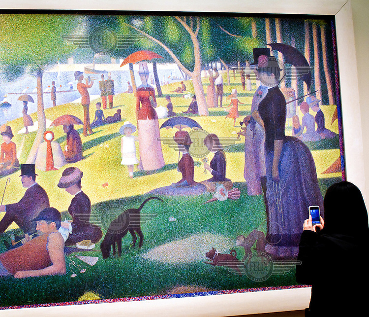 A woman takes a photo of Georges Seurat's 'A Sunday Afternoon on the Island of La Grande Jatte', displayed at the Art Institute of Chicago, Illinois.