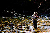 An angler ties on a fly while fishing on Rio Chimehuin in northern Patagonia near Junin de los Andes, Argentina.