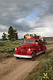 USA, Wyoming, Encampment, kids ride an old restored firetruck to a dinner cookout, Abara Ranch