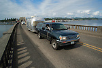 Toyota towing travel trailer on bridge.