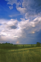 An aproaching storm cloud hides most of a rainbow in the skies over North Sterling State Park, Morgan County, Colorado