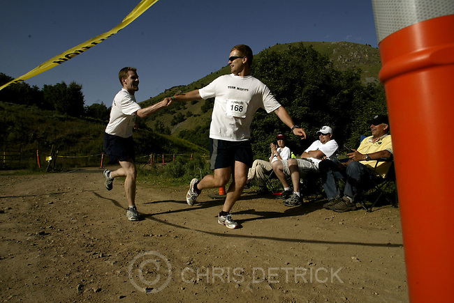 Logan,Utah--6/17/2005- .Jon Allen, left, of Logan, hands off the slap bracelet to his relay partner Jason Brimhall at the 8th exchange in the Cache National Forest during the two day, 170 mile long Wasatch Back Relay Race.  100 teams with either six or 12 members competed in the race which started at the Hardware Ranch in Logan and  ended in Park City. The race was split into 36 section, each with varying lengths and difficulties,  in which the team members each  took turn running .Photo By: Chris Detrick /Salt Lake Tribune.
