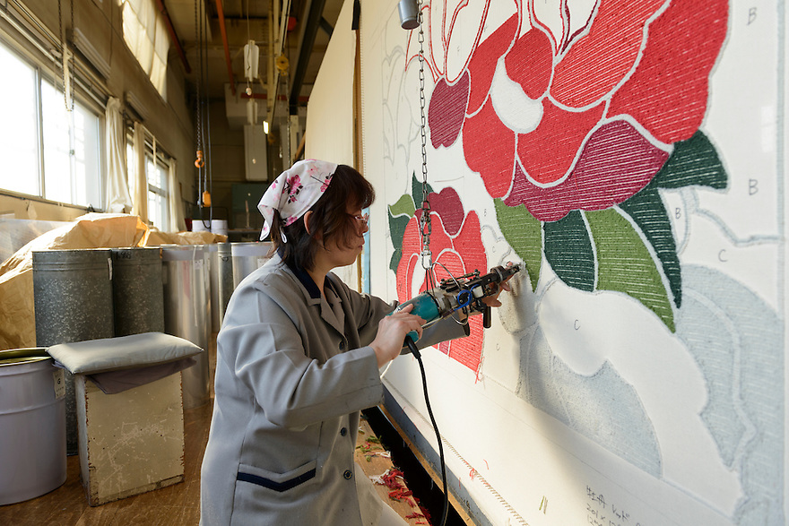 Working on a machine-made tufted carpet. Oriental Carpet Mills, Yamanobe-machi, Yamagata, Japan, April 11, 2016. Oriental Carpet Mills was founded in 1935 and produces luxury hand-woven and tufted carpets. Its carpets are used all over the world, including in the Vatican, the Imperial Palace in Tokyo and the Kabukiza Kabuki Theatre.