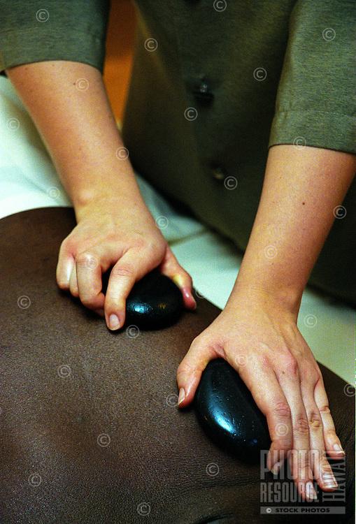 Closeup of pohaku, hot stone therapy, a Hawaiian healing therapy practiced at many spas